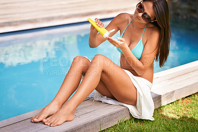 Buy stock photo A beautiful woman applying sunscreen to her body while sitting by the pool