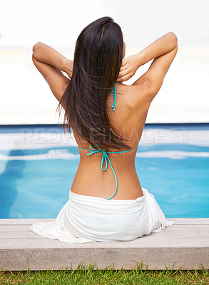 Buy stock photo Rear view shot of a young woman relaxing by a swimming pool