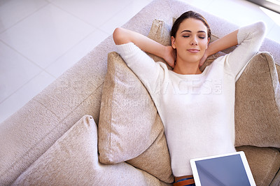 Buy stock photo Shot of a young woman lying on a sofa with a digital tablet