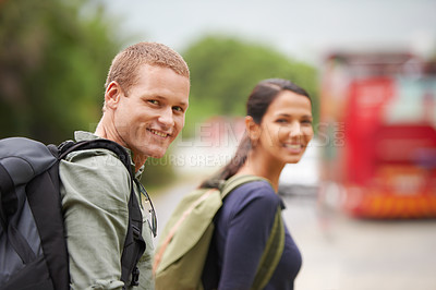 Buy stock photo A travelling couple smile at the camera while waiting for their bus to arrive