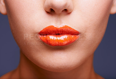 Buy stock photo Cropped shot of a woman's lips covered in shiny orange lipstick