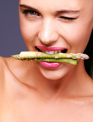 Buy stock photo Portrait of a woman biting on a bunch of asparagus in studio
