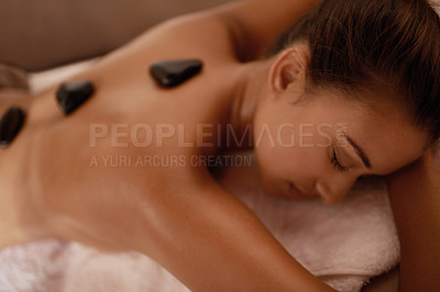 Buy stock photo Shot of a young woman enjoying hot stone therapy at a spa