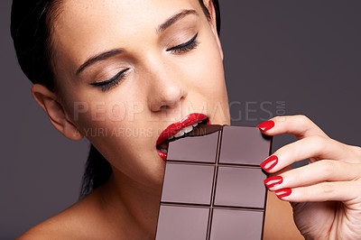 Buy stock photo Closeup portrait of a cute young female biting into a piece of chocolate