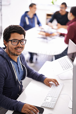 Buy stock photo Cropped shot of a young man working on his laptop in an office