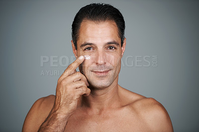 Buy stock photo Studio shot of a handsome mature man applying moisturizer to his skin