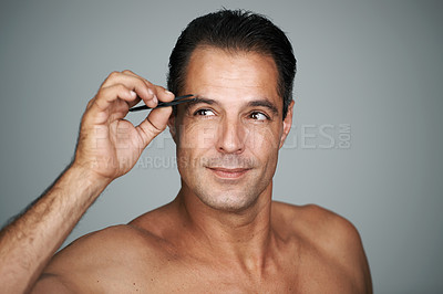 Buy stock photo Studio shot of a handsome mature man trimming his eyebrows with tweezers