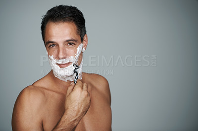 Buy stock photo Studio portrait of a handsome mature man shaving his face