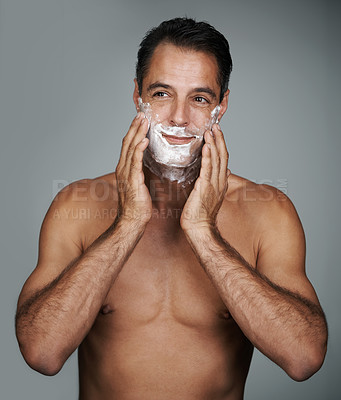 Buy stock photo Studio shot of a handsome mature man applying shaving cream to his face