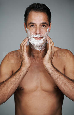 Buy stock photo Studio portrait of a handsome mature man applying shaving cream to his face
