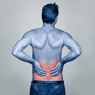 Buy stock photo Rear view studio shot of a mature man holding onto his aching back that is highlighted in red