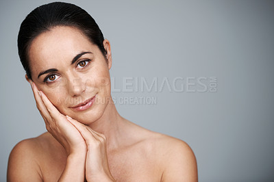 Buy stock photo Cropped studio portrait of a beautiful mature woman touching her face