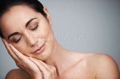 Buy stock photo Cropped studio shot of a beautiful mid adult woman with her eyes closed touching her face