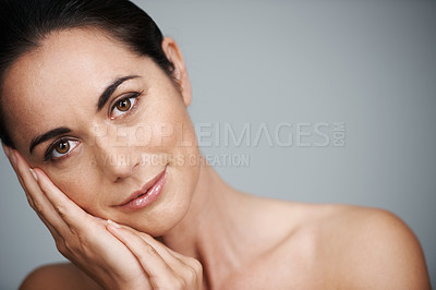 Buy stock photo Cropped studio shot of a beautiful mid adult woman touching her face