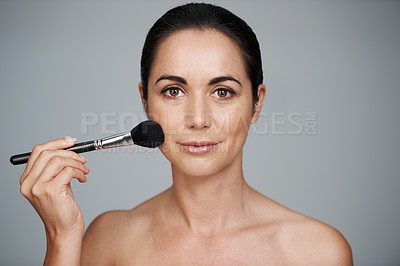 Buy stock photo Cropped studio portrait of a woman applying blusher to her cheeks with a make-up brush