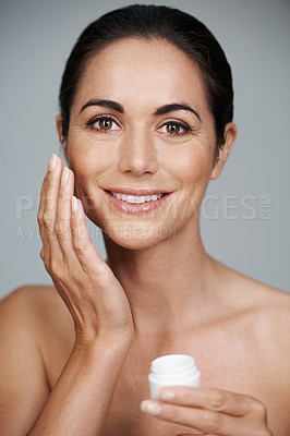 Buy stock photo Cropped portrait of a beautiful mature woman applying moisturizer to her skin