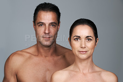 Buy stock photo Studio portrait of a mature couple standing close together against a gray background