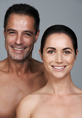 Buy stock photo Studio portrait of a happy mature couple standing close together against a gray background