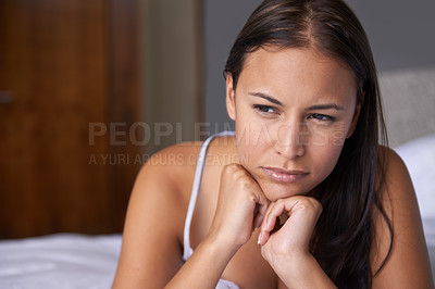 Buy stock photo Cropped shot of a young woman lying on her bed looking thoughtful
