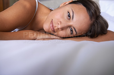Buy stock photo Closeup portrait of a young woman lying on a bed