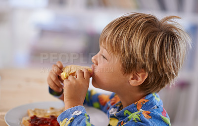 Buy stock photo A cute little boy eating toast with peanut butter and jam