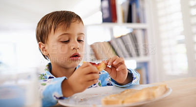 Buy stock photo A cute little boy eating toast with jam and peanut butter