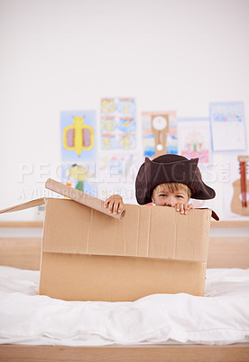 Buy stock photo Portrait of a little pirate hiding in a cardboard box
