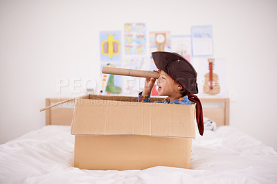 Buy stock photo A little pirate spying land from his cardboard box boat
