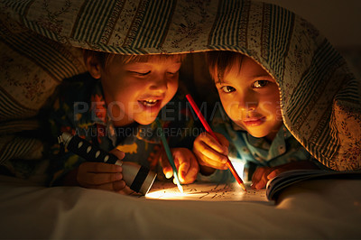 Buy stock photo Portrait of two brothers lying underneath their blanket coloring in pictures with a flashlight