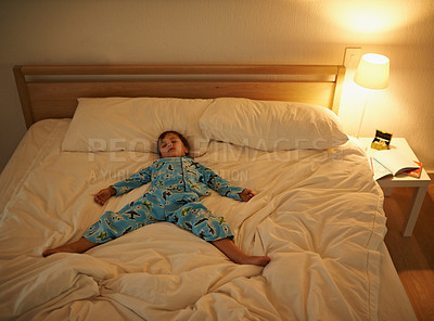 Buy stock photo Shot of a young boy sleeping in bed