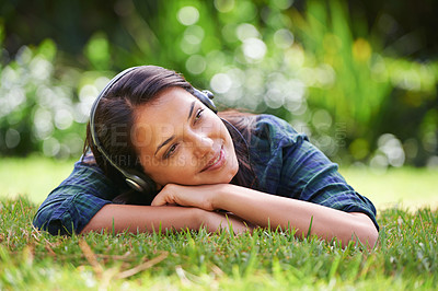 Buy stock photo Shot of an attractive young woman lying on the grass and listening to music