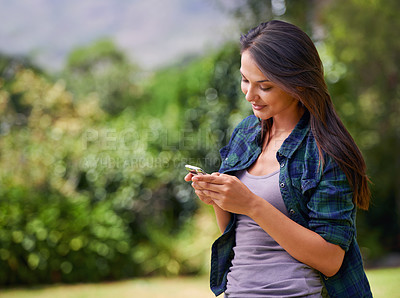 Buy stock photo Shot of an attractive young woman using her cellphone outside in a garden