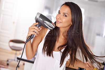 Buy stock photo Shot of a beautiful young woman blow drying her hair