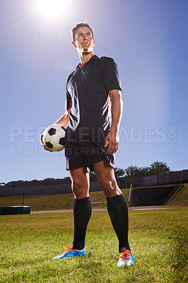 Buy stock photo Shot of a young footballer standing on a field with a ball in his hands