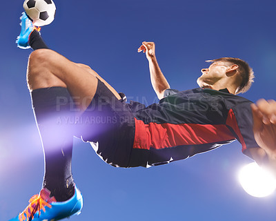 Buy stock photo Shot of a young footballer kicking a ball in mid-air