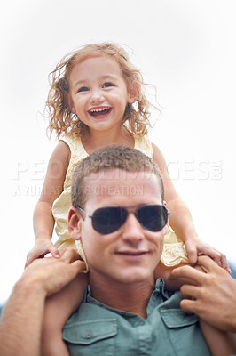 Buy stock photo Portrait of a young father wearing sunglasses while carrying his daughter on his shoulders