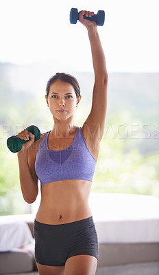 Buy stock photo A portrait of a beautiful young woman lifting dumbbells at home