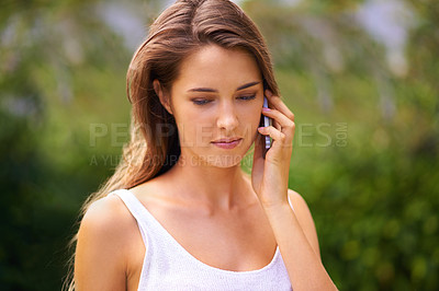 Buy stock photo Cropped shot of an attractive young woman using her cellphone outdoors