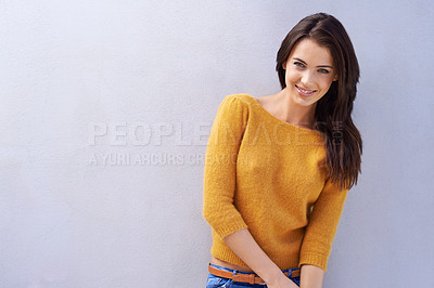 Buy stock photo Portrait of a beautiful young woman standing against a gray wall