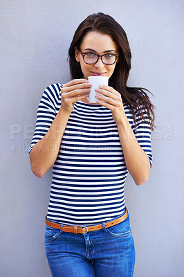 Buy stock photo Portrait of a an attractive woman holding a coffee cup against a gray background