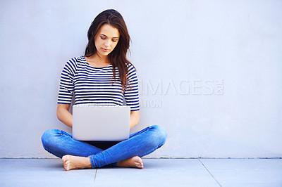 Buy stock photo Full length shot of an attractive young woman sitting cross legged using a laptop
