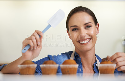 Buy stock photo A happy young woman about to apply frosting to her freshly-baked batch of cupcakes