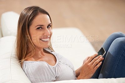 Buy stock photo Portrait of a woman smiling at the camera while using her phone