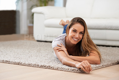 Buy stock photo Portrait of a woman smiling at the camera while lying on her living room floor