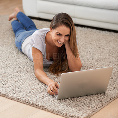 Buy stock photo A woman lying on her living room floor while using her laptop