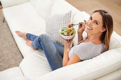 Buy stock photo A young woman enjoying her salad with a smile