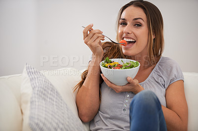 Buy stock photo Portrait of a beautiful woman sitting on her sofa while eating her salad