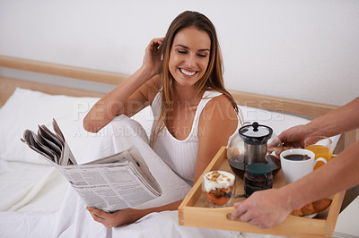 Buy stock photo Shot of a beautiful young woman being treated with breakfast in bed