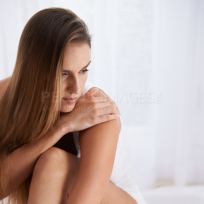 Buy stock photo Shot of a beautiful young woman sitting serenely on her bed