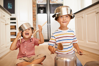 Buy stock photo Two young boys sitting on the kitchen floor playing with pots and pans